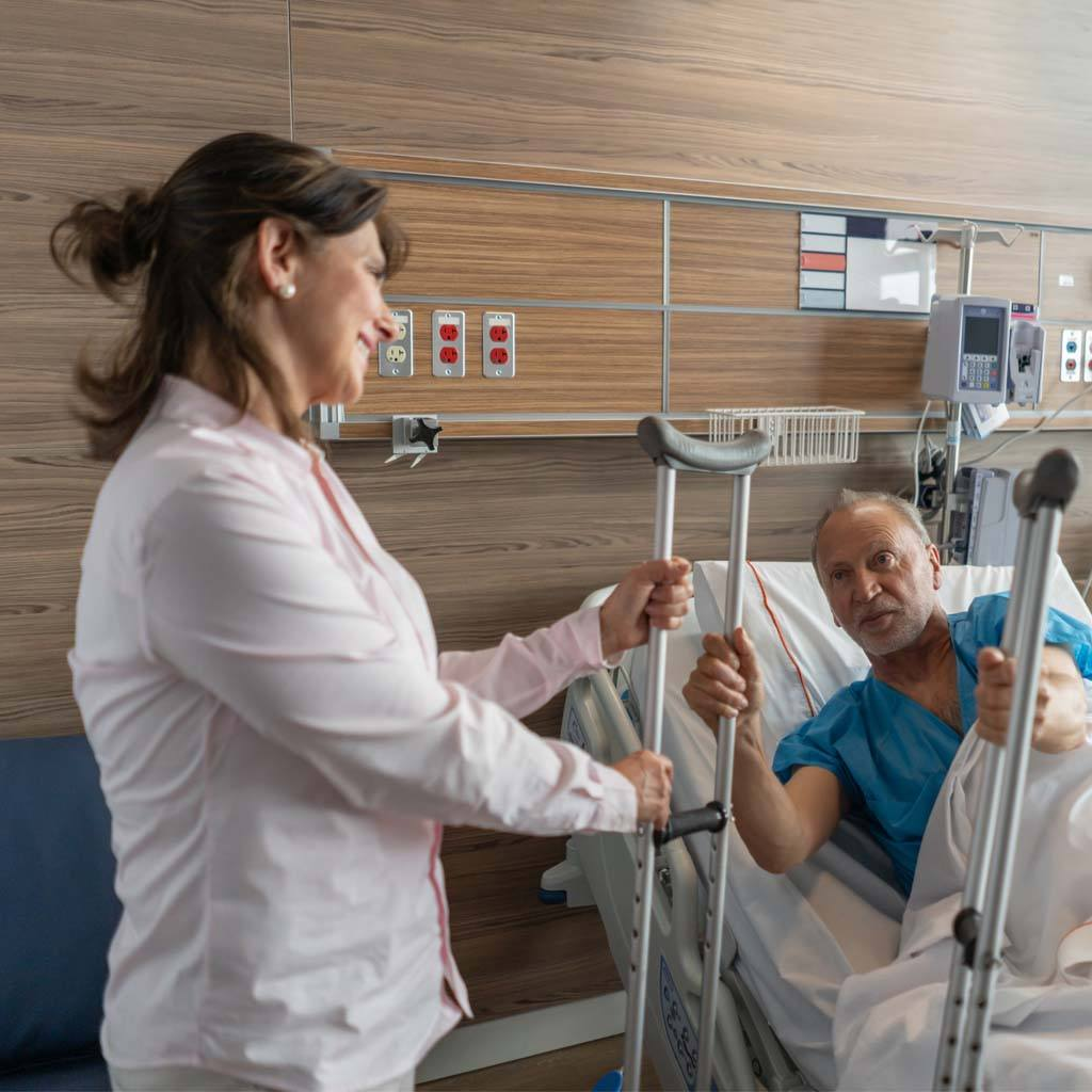 Cheerful female spouse handing crutches to partner while he is sitting down on hospital bed both smiling