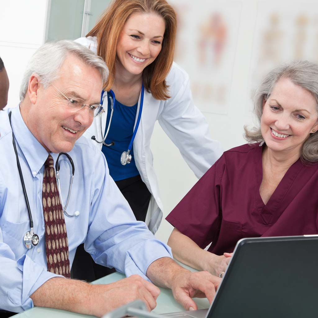 Happy Medical Team Looking at Laptop in Doctor's Office.