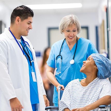 Nurse and doctor talking to happy hospital patient after surgery
